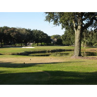The par-3 14th hole at the Barony Course at Port Royal Golf Club is over water to a green with water on one side, sand on two others.