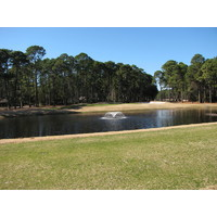 Oyster Reef Golf Club's 11th hole, a par 3, is a short shot over water to a large green.