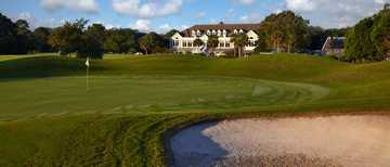 A view of a green and the clubhouse at Country Club of Hilton Head